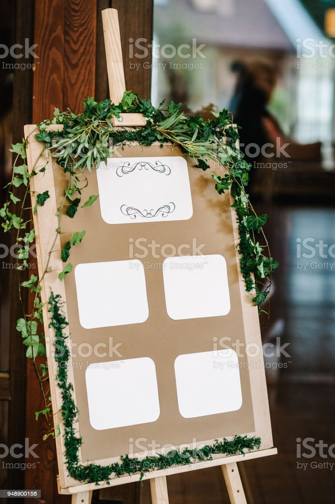List, plan, chart of the seating area of guests at the tables at restaurant. Tables wedding guests on the easel on wedding reception. The frame is decorated with green flowers and greenery. stock photo