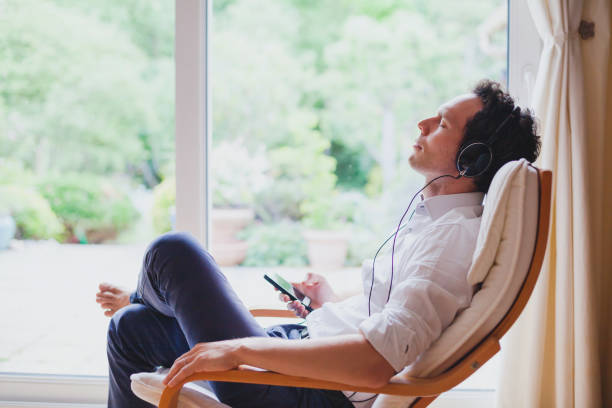 Listen relaxing music at home, relaxed man sitting in headphones. listening relaxing music at home, relaxed man in headphones sitting in deck chair in modern bright interior headphones stock pictures, royalty-free photos & images