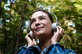 Woman is listening music at the park.