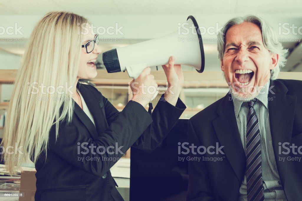 Listen to my Ideas! Businesswoman shouting with Megaphone to Senior Manager stock photo