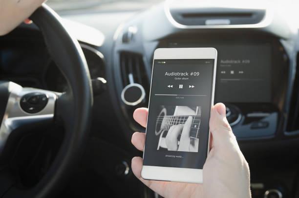 lyssna på musik. smart telefon ansluten till bilens ljudsystem. - audioutrustning bildbanksfoton och bilder
