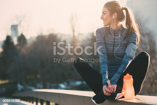 Young beautiful woman resting after the jogging in the city.She is listening to the music.