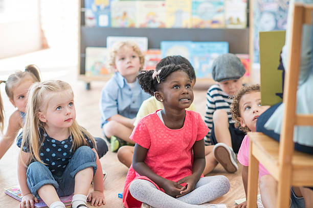 listening to a teacher read a book - preschool student stock photos and pictures