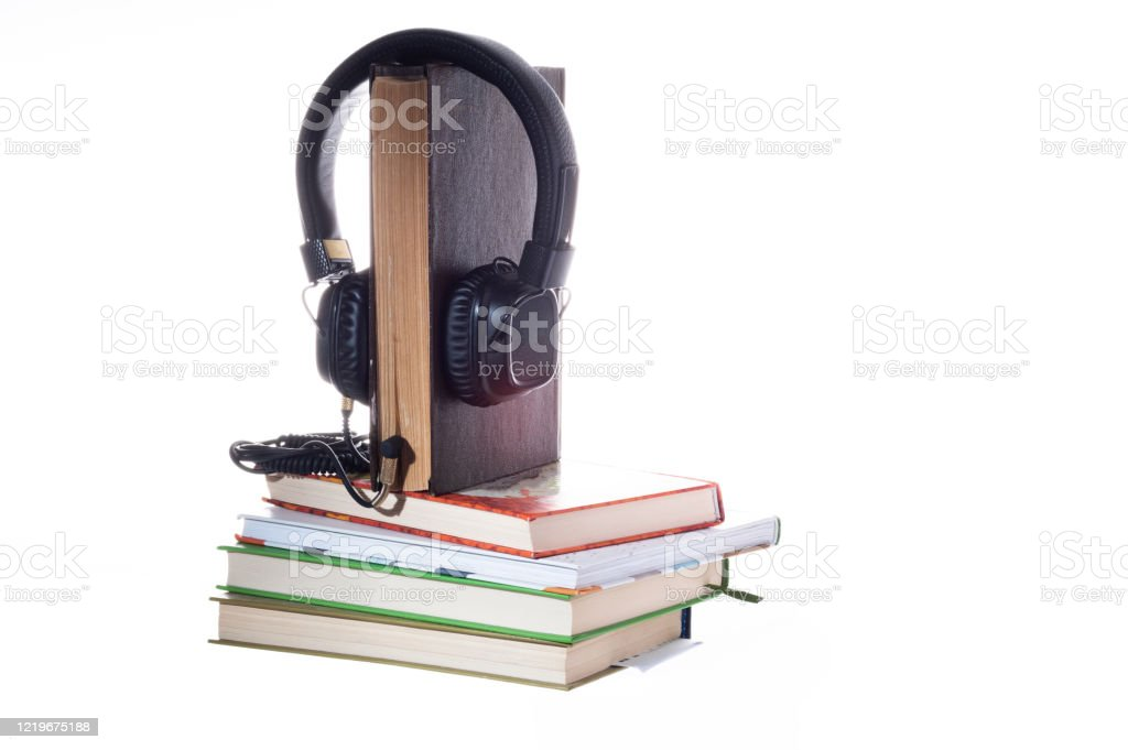 Listening to books through headphones. Listening to stories through books. Live book and headphones. Listening to books through headphones. Listening to stories through books. Live book and headphones. Isolate. Abandoned Stock Photo