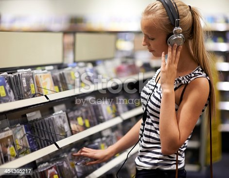 A pretty young woman listening to music on headphones at the store