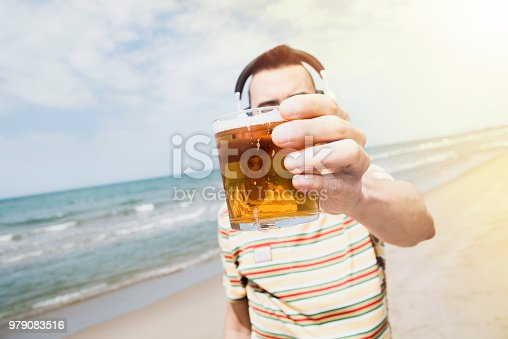 closeup of a young caucasian man on the beach listening to music with a pair of wireless headphones while is drinking a beer in front of the sea, with a sunbeam in the background