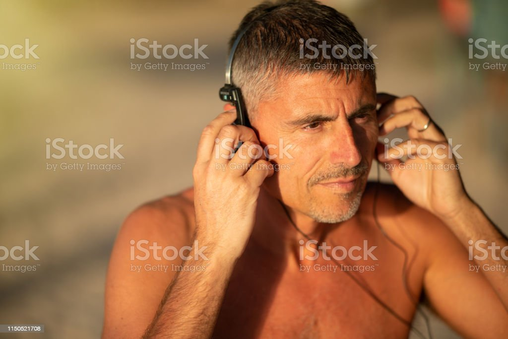 Listening to music. Handsome man on vacation listening to music on...