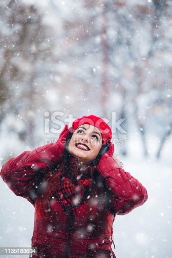 Young beautiful woman in listening to music over headphones in a snow covered park