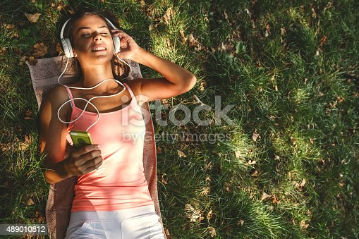 Beautiful Young Woman with Headphones lying on grass and listening to music