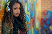 A female teenager of African descent is sitting alone in front of a graffiti-covered wall. She is wearing headphones and looking forward into the distance with a serious expression.