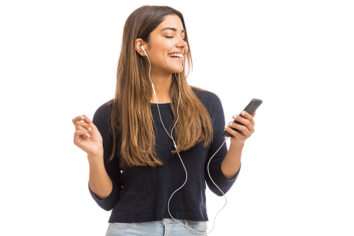 Young stylish woman wearing earphones while using phone over white background