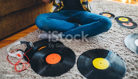 Young woman listening to old records. Sitting on the floor.