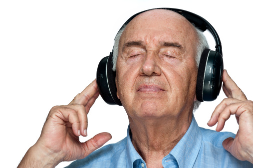Senior man listening to the music with his headphones on white background