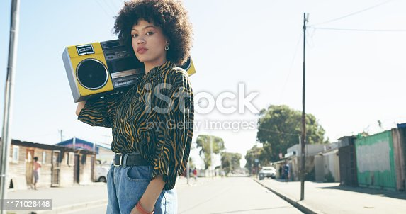 Shot of an attractive young woman listening to music on a boombox in an urban setting