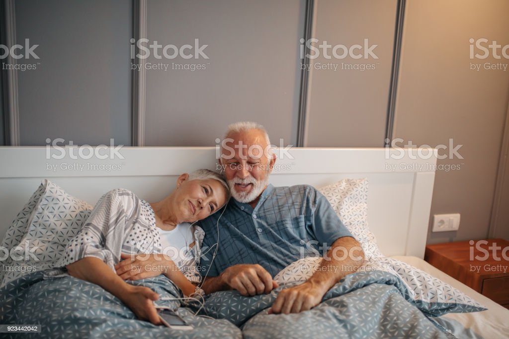 Elderly couple listening to the music in bed