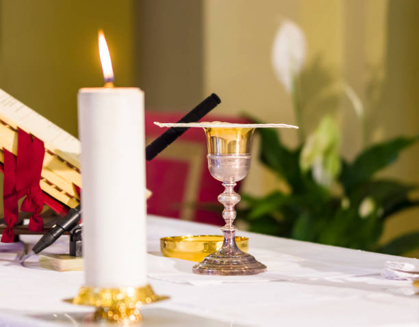 lit candle illuminates chalice with wine and ciborium with the host, ready for the communion of the faithful stock photo