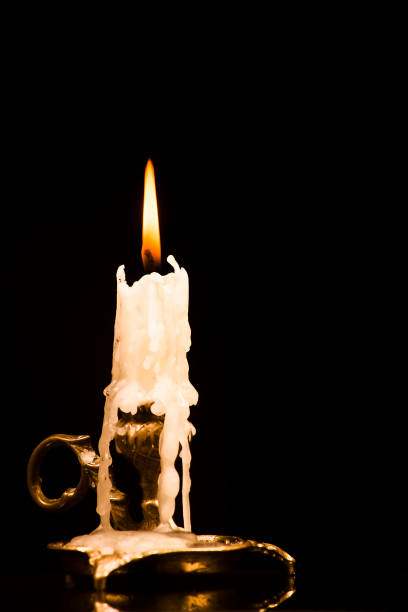 lit candle in a candlestick on a black background - perdita di peso foto e immagini stock