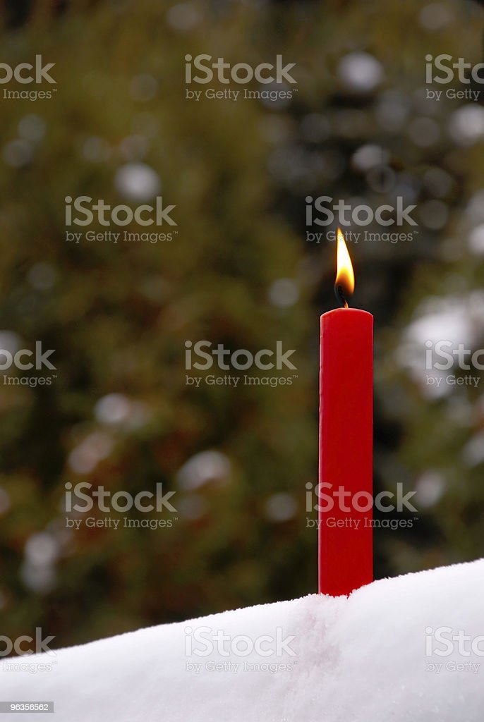 Lit Candle in Snow Outside royalty-free stock photo