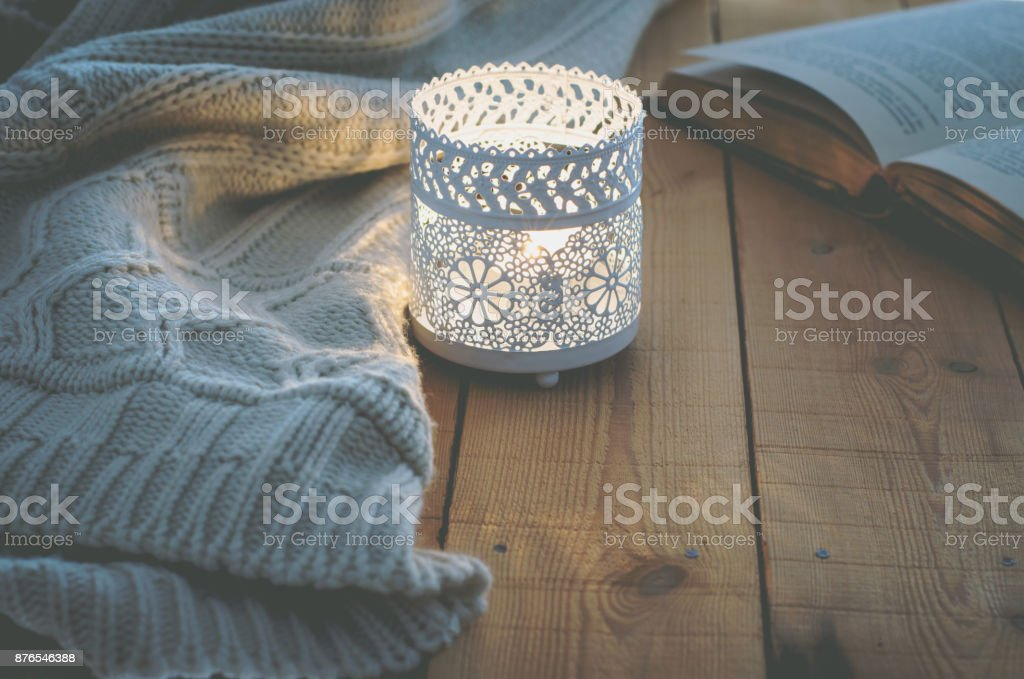 Lit Candle White Knitted Sweater Open Book on Plank Wood Table by Window. Cozy Winter Autumn Evening. Natural Light Authentic Tranquil Atmosphere. Kinfolk Hygge Slow Living Style. Matte Toned stock photo