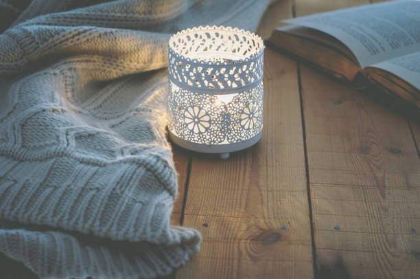 lit candle white knitted sweater open book on plank wood table by window. cozy winter autumn evening. natural light authentic tranquil atmosphere. kinfolk hygge slow living style. matte toned - candle stock pictures, royalty-free photos & images