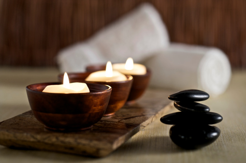 SEVERAL MORE IN THIS SERIES. Floating aromatherapy candles in wooden bowls and black massage stones rest in a zen spa atmosphere.  Very shallow DOF.