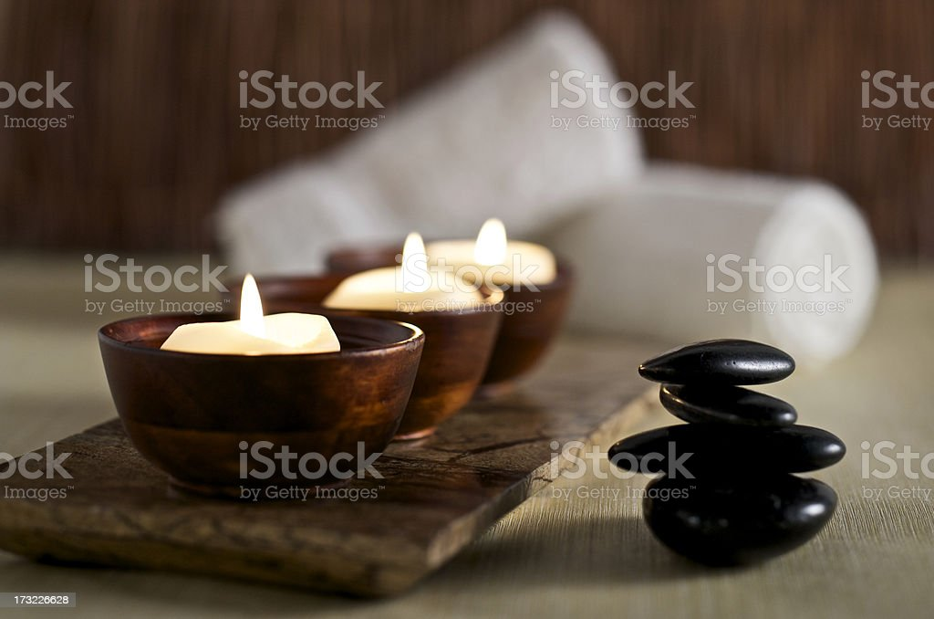 Lit candles and black massage stones in Zen spa stock photo