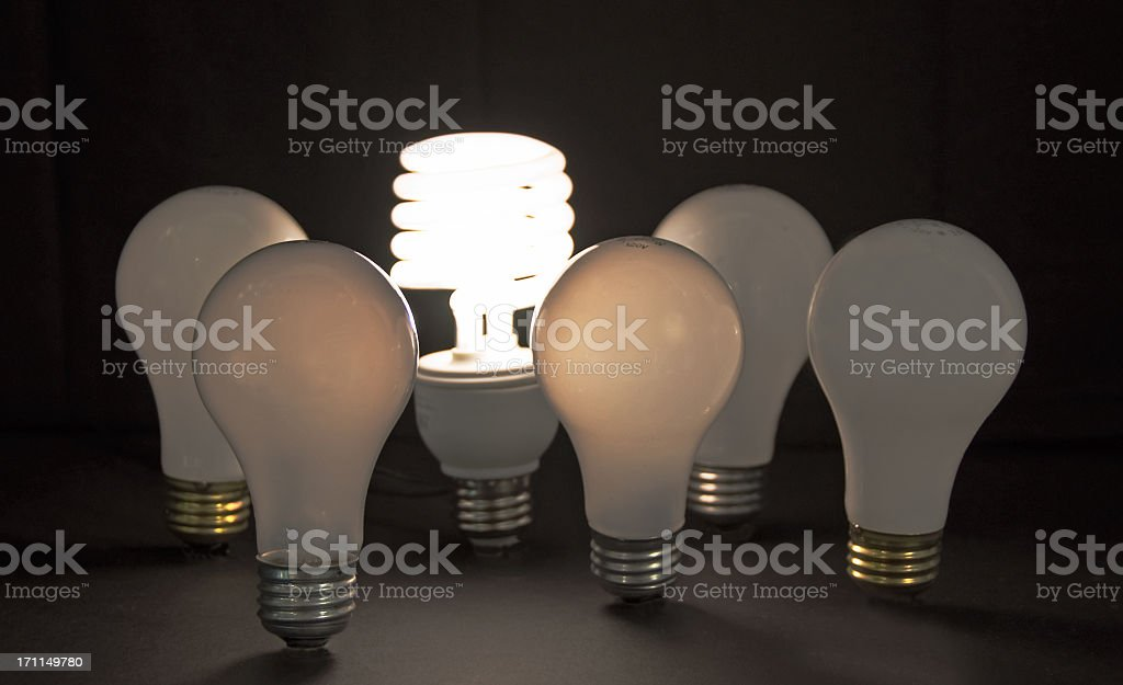 1 lit CFL light bulb circled by 5  incandescent bulbs stock photo