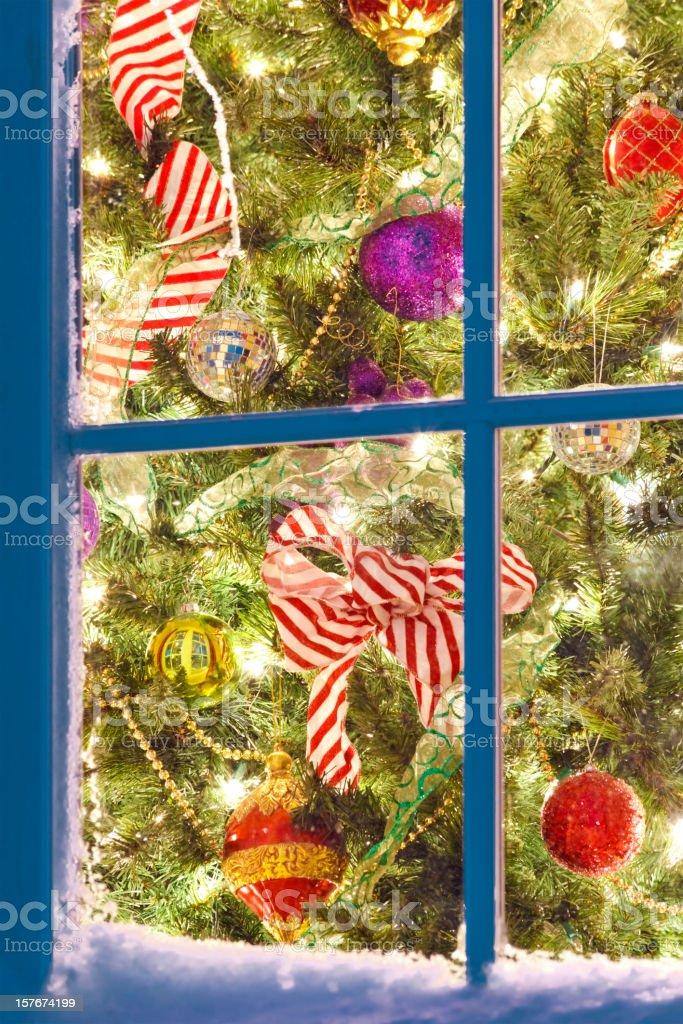 lit Christmas tree through snowy window panes stock photo