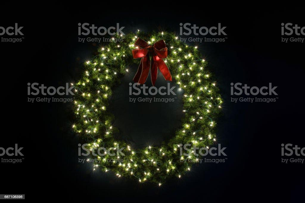 Lit Christmas Wreath on Navy Wall Lizenzfreies stock-foto