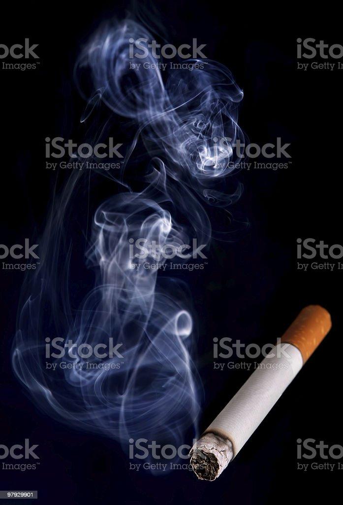 A lit cigarette emitting smoke on a black background royalty-free stock photo