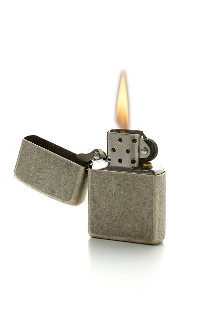 A lit cigarette lighter with the gray top folded open stock photo