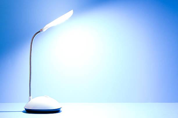lit desk lamp - bürolampe stock-fotos und bilder