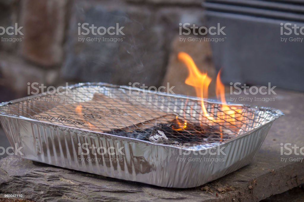 A lit disposable BBQ stock photo