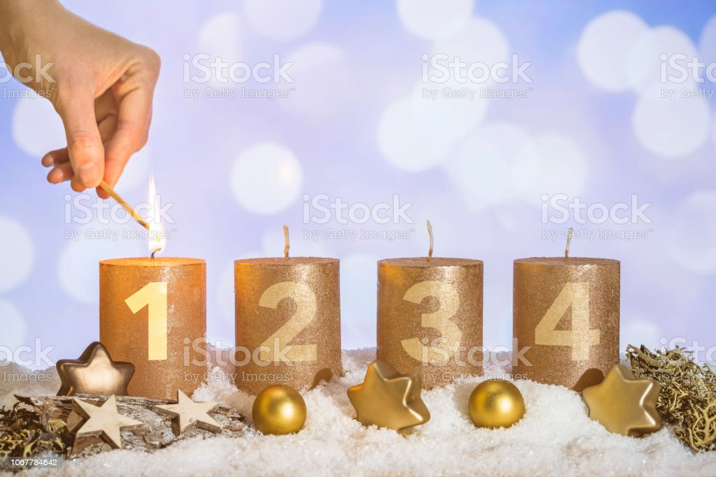 Four numbered gold advent candles with first candle lit by hand with...