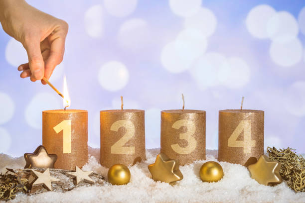 Lit first advent candle in snow by match in hand stock photo