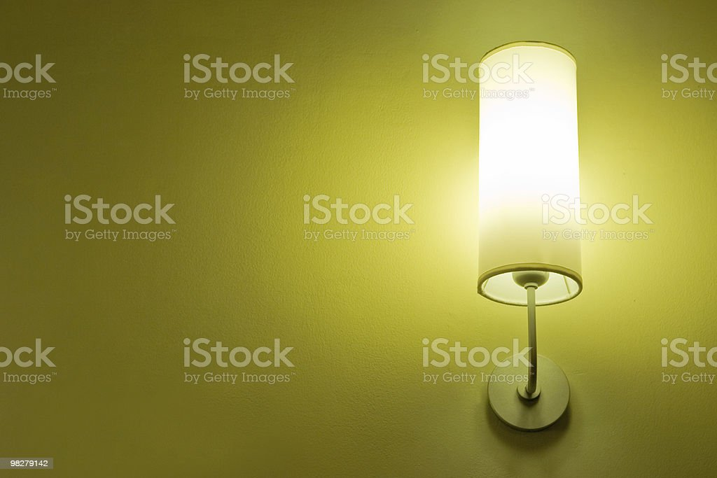 A lit lamp on a yellow wall in the room royalty-free stock photo