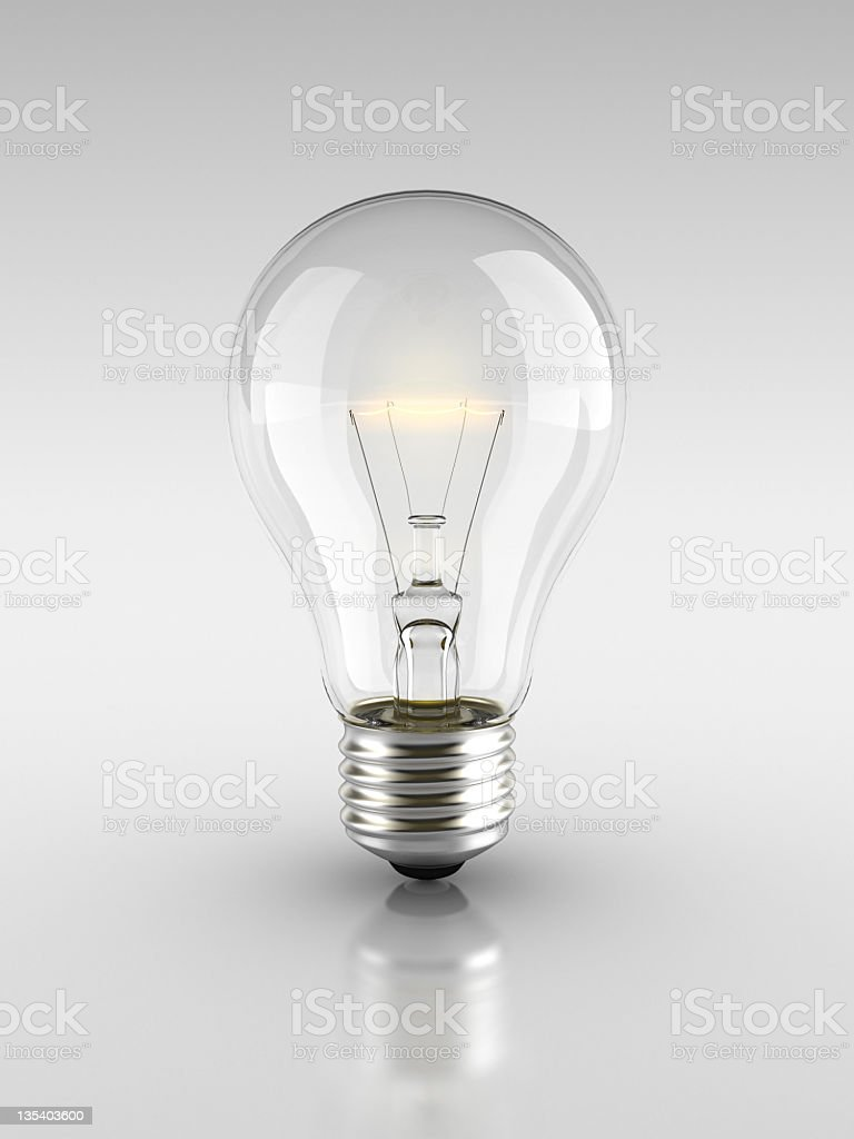 Lit light bulb on a grey background  stock photo