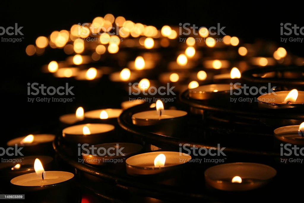 Lit praying candles in a temple stock photo
