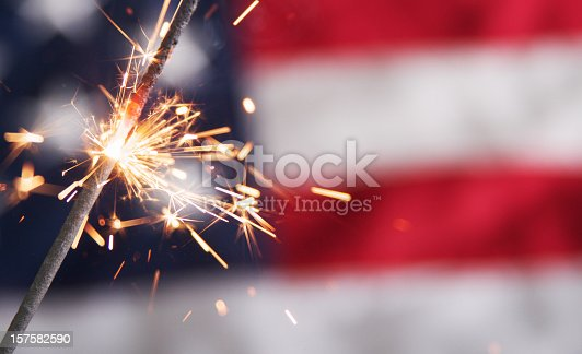A close-up view of a single burning sparkler. Sparks are flying in front of a partial, blurry view of an American flag in the background.