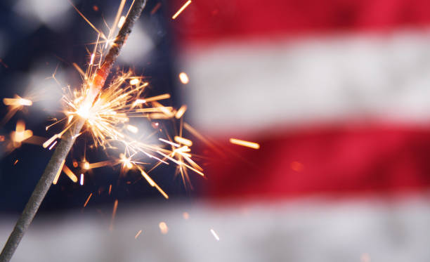 Lit sparkler against a blurred American flag A close-up view of a single burning sparkler. Sparks are flying in front of a partial, blurry view of an American flag in the background. independence day photos stock pictures, royalty-free photos & images