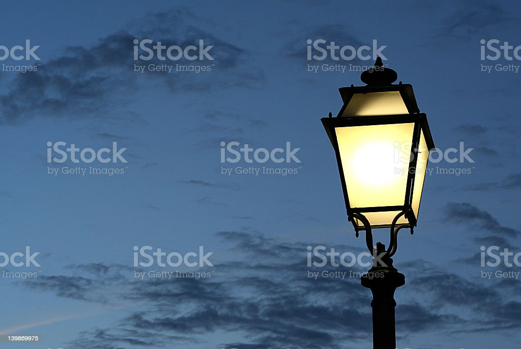 Lit street lamp against a cloudy dark sky stock photo