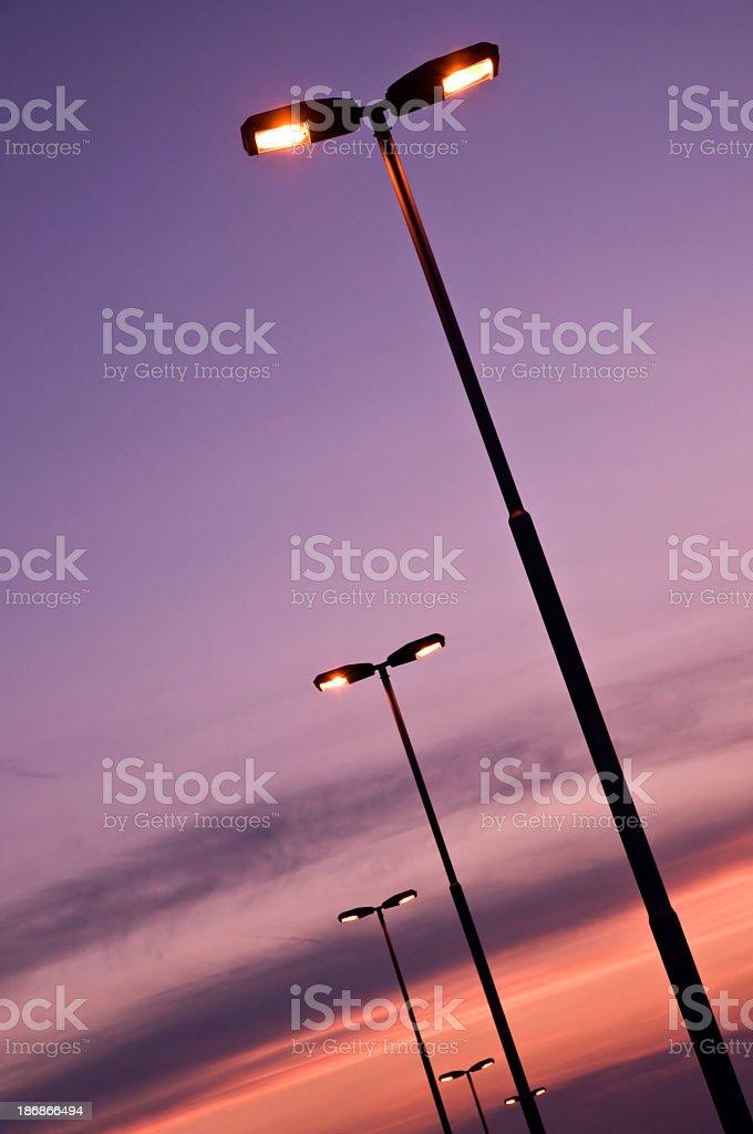 Lit street lamps on sunset background stock photo
