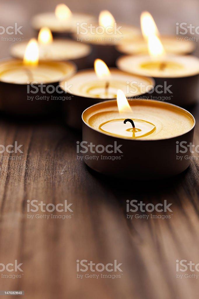 Lit tea lights on a wooden table stock photo