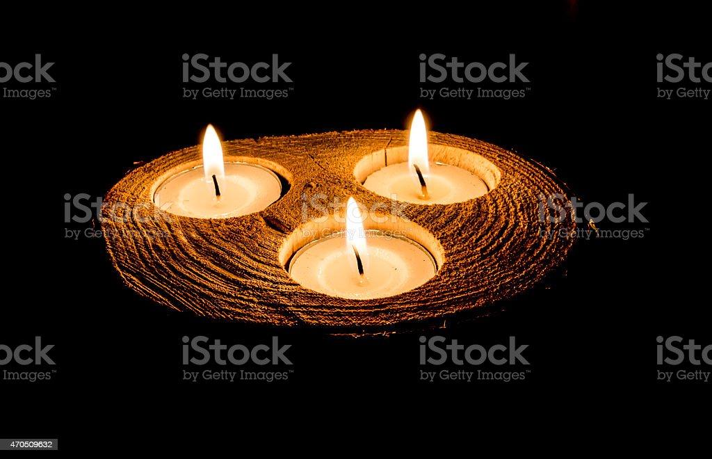Lit Triplet Tea Lights on a dark background stock photo
