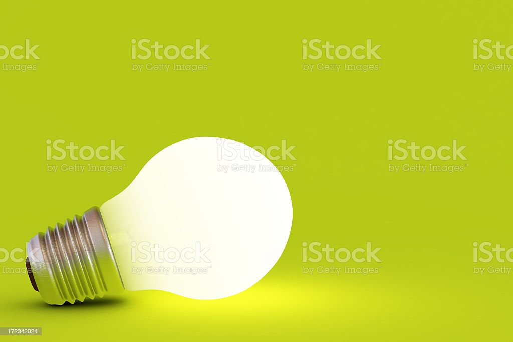 A lit up light bulb on a green background royalty-free stock photo