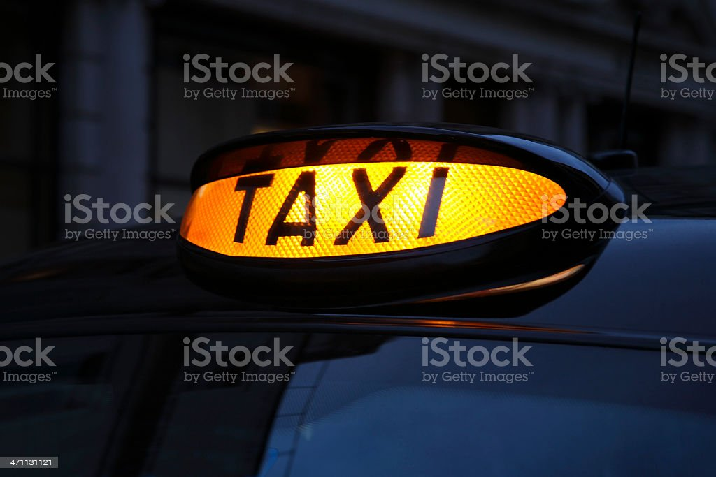 Lit up yellow taxi sign at night stock photo