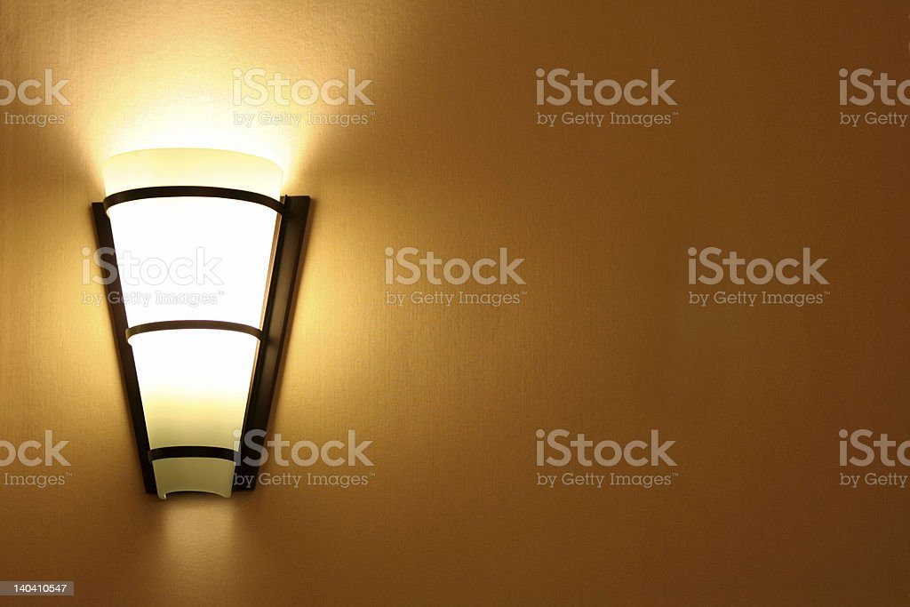 A lit wall lamp on an orange wall stock photo
