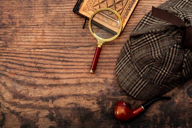 Ficción literaria, investigar el crimen y la historia de misterio idea conceptual con sherlock holmes detective sombrero, pipa humeante, lupa retro y viejo libro aislado en la mesa de madera con espacio de copia - foto de stock