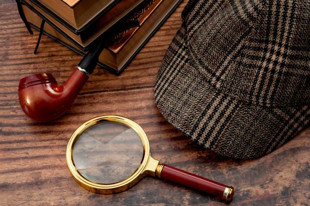 Ficción literaria, inspector de policía, investigar el crimen y la historia de misterio idea conceptual con sherlock holmes detective sombrero, pipa humeante, lupa retro y libro aislado en la mesa de madera - foto de stock
