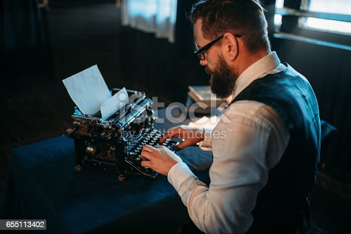 655113470 istock photo Literature author in glasses typing on typewriter 655113402